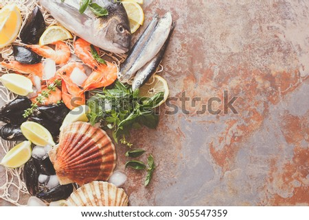 Seafood assortment. Overhead shot of raw scallops, fish, shrimps and mussels with lemon and spices  on crushed ice. Preparing food concept - stock photo