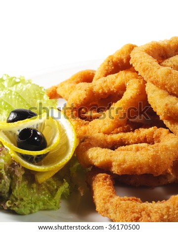 Seafood - Fried Calamari. Deep-fried Squid Dressed with Salad Leaves, Parsley, Olives and Lemon - stock photo