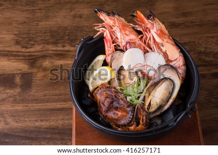 Seafood in Iron bowl,  Korean food on wooden background - stock photo