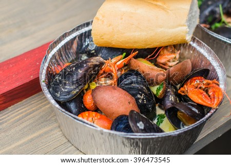 Seafood - mussels and crayfish with vegetables . A bowl of seafood at a street market . Close- up of a plate of foil on a wooden table .