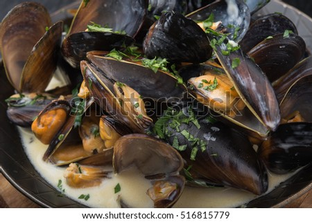 seafood mussels on pan with cream sauce. restaurant food