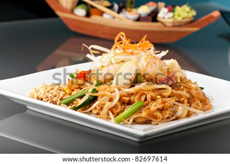 Seafood pad Thai dish of stir fried rice noodles on a square white plate with chopsticks and grated carrot garnish. - stock photo