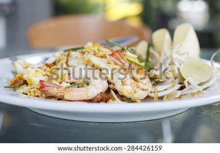 Seafood pad Thai dish of Thai fried rice noodles on a square white plate with chopsticks and grated carrot garnish. - stock photo