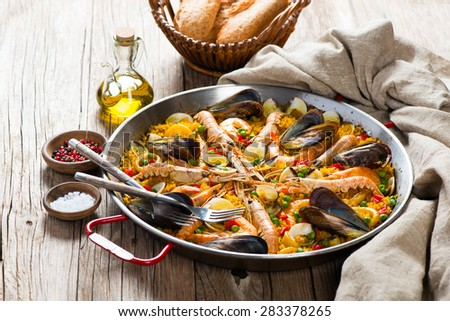 Seafood paella in the fry pan on a wooden rustic table - stock photo