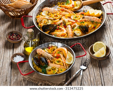 Seafood paella on paelleras with olive oil, spices and lemon on wooden table - stock photo
