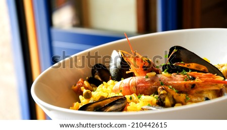 Seafood paella with chicken casserole and chorizo sausage in rustic restaurant. Opened blue door to the balcony. - stock photo