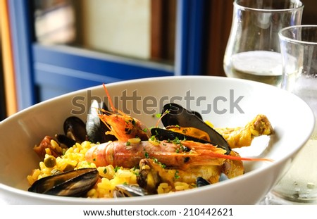 Seafood paella with chicken casserole and chorizo sausage served with cold white wine in rustic restaurant. Opened blue door to the balcony.