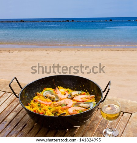 Seafood paella with glass of wine in seaside cafe - stock photo