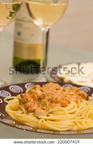 seafood pasta dish and white wine on a table  - stock photo