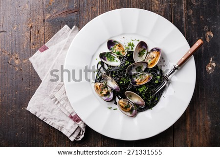 Seafood pasta with clams Spaghetti Vongole on white plate on dark marble background - stock photo
