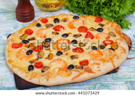 seafood pizza with shrimps, mussels, tomatoes and olives