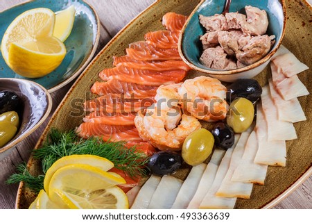 Seafood platter. Fresh cod liver, salmon, shrimp, slices fish fillet, decorated with herb, lemon and olives on light wooden background. Mediterranean appetizers. Top view