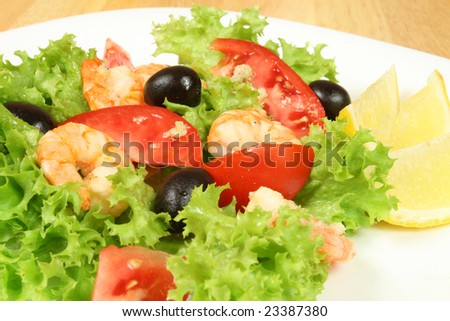 Seafood salad on a plate. Shrimps, lettuce, olives, tomato.