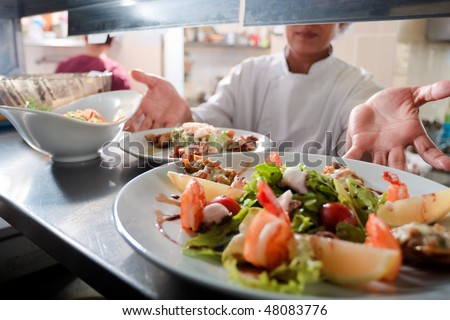 Seafood salad with stuffed mussel and prawns on commercial kitchen - stock photo