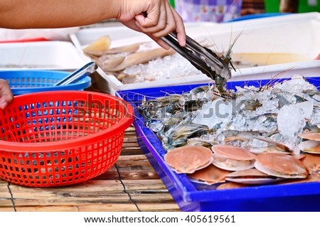 seafood shopping in the fresh market, fresh shrimps and scallops for sale - stock photo