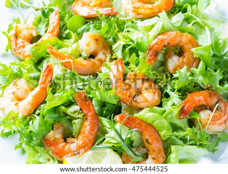 Seafood shrimp prawns. Shrimp lettuce salad on white plate with lemon rosemary arugula on white wooden background. Healthy food or diet concept.