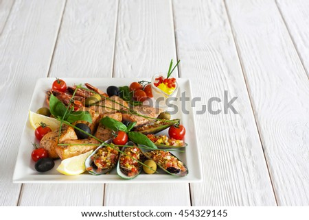 Seafood snack on white wooden background. Closeup of plate with grilled shrimps, salmon and stuffed mussels. Copyspace for text or advertising - stock photo