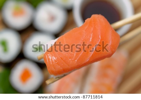 Seafood, Sushi and Chopsticks - traditional sushi and rolls on the dish in background
