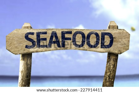 Seafood wooden sign with a beach on background - stock photo