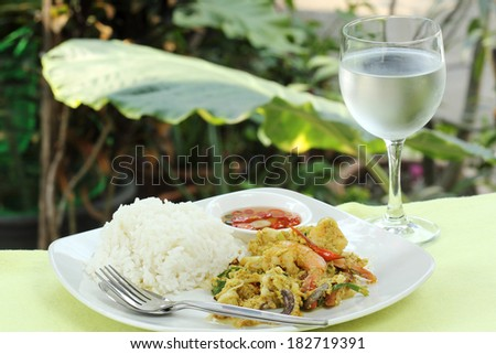 Seafood yellow curry powder stir Fried with steam rice on the place and the glass of water