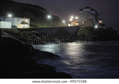 Seafront houses on a rocky coastline at night - stock photo