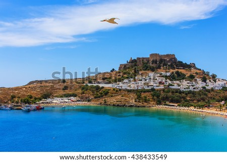 seagull flies over a beautiful cove beach Lindos acropolis ships dock - stock photo