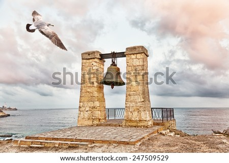 Seagull flies over  bell of Chersonesos in Chersonesos Taurica, Crimea - stock photo