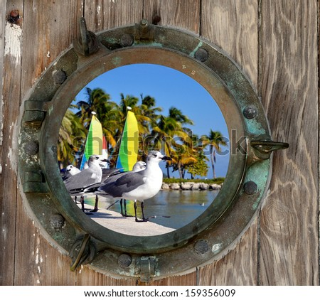 Seagulls and Sailboats on Smathers Beach in Key west, Florida looking through a rustic old porthole. - stock photo