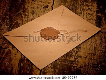 sealed brown envelope on wood background - stock photo