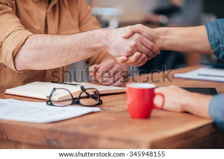 Sealing a deal. Close-up of two men shaking hands while sitting at the wooden desk  - stock photo