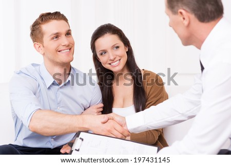 Sealing a deal. Happy young man shaking hand to financial agent while sitting together with his wife - stock photo