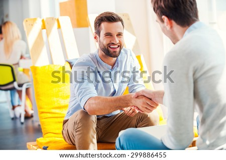 Sealing a deal! Two happy young men shaking hands while sitting in the rest area of the office - stock photo