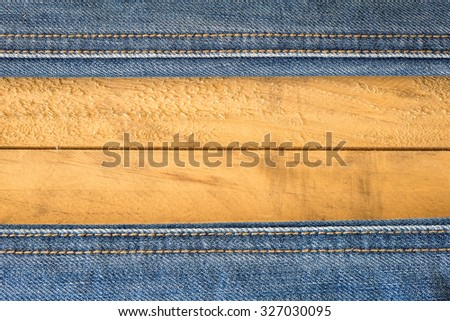 Seam of Blue Jeans on wooden Texture - stock photo