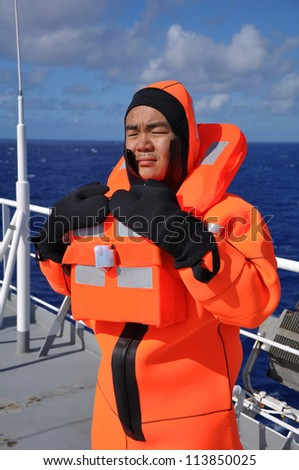 seaman in immersion suit  during lifeboat drill on board of vessel - stock photo