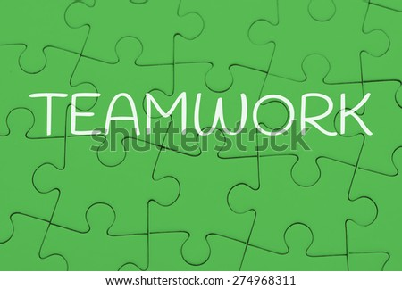 Seamless green puzzle piece background pattern with the word teamwork. Conceptual image of connection, solution and business strategy. - stock photo