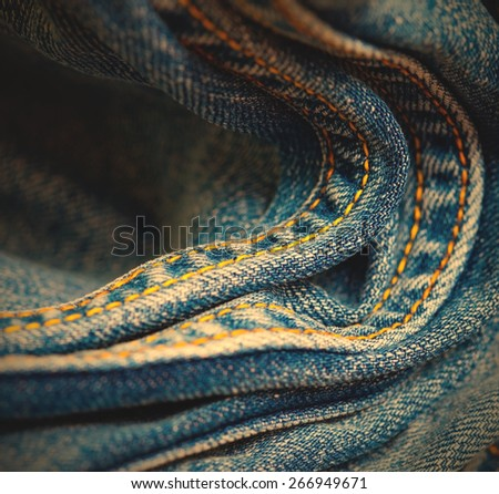 seams with yellow thread on blue jeans, close-up. instagram image retro style - stock photo