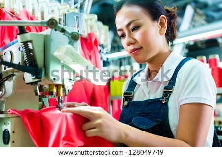 Seamstress or Chinese worker in a factory sewing with a industrial sewing machine, she is very accurate - stock photo