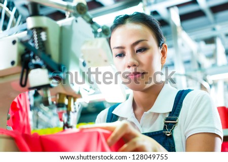 Seamstress or worker in a factory sewing with a industrial sewing machine, she is very accurate - stock photo