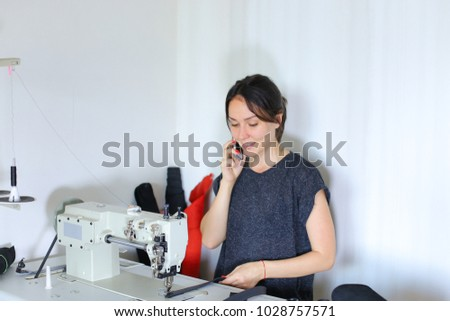 Seamstress sewing belt using sewing machine. Girl working at factory, female with red nails and bracelet sitting near table in workshop stitching black leather strap using special mechanism.