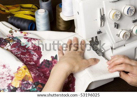 Seamstress sewing on overstitching machine. Sewing items on table. - stock photo