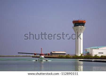 Seaplane landing on the water with the air traffic control tower in the background - stock photo