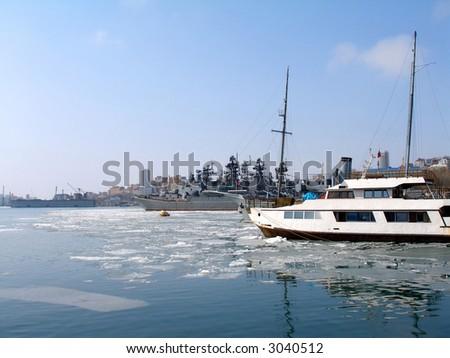 Seaport Vladivostok, spring, floating of ice, moored yachts, war ships - stock photo