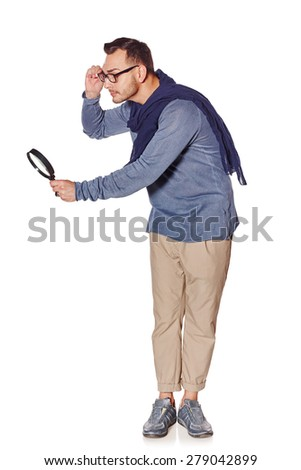 Search concept. Side view of full length serious man looking through magnifying glass at blank copy space, over white background.  - stock photo