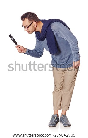 Search concept. Side view of full length serious man looking through magnifying glass at blank copy space down, over white background.  - stock photo