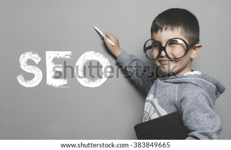 Search engine optimization, boy with glasses and funny gesture writing on the blackboard the text SEO