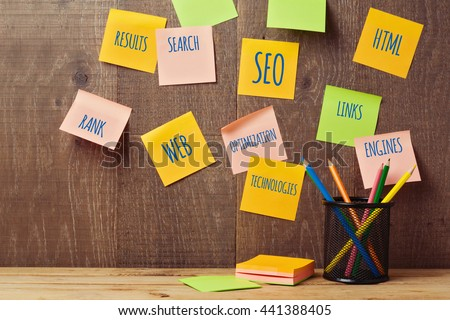 Search engine optimization SEO concept with notes on wooden wall - stock photo