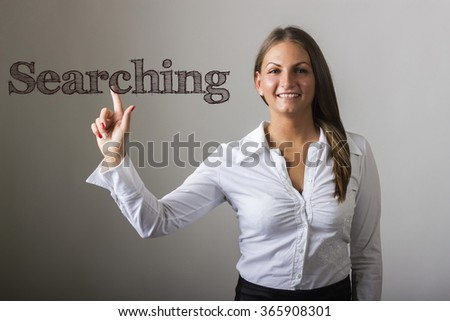 Searching - Beautiful girl touching text on transparent surface - horizontal image - stock photo