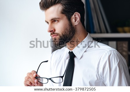 Searching for the right solution. Portrait of handsome young businessman carrying his glasses in hand and looking away while standing in office  - stock photo
