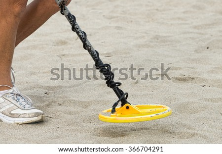 Searching for treasure with a metal detector - stock photo