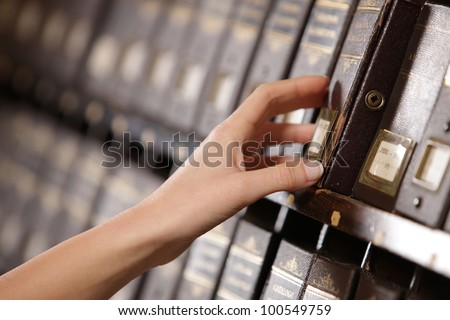 Searching in archives. Student hands searching from a filling cabinet. - stock photo
